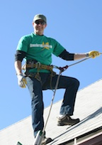 Denver Gutter Cleaning - Brian Flechsig roped off on a roof to clean the gutters