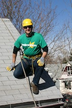 Brian Flechsig of Denver Gutter Cleaning roped off of a roof to clean the rain gutters